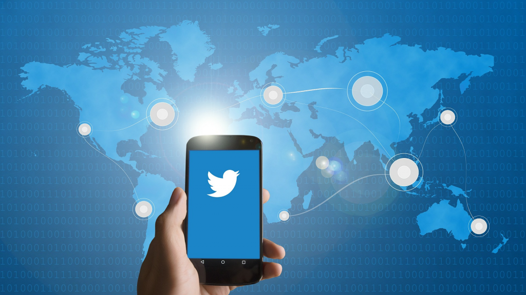 Logo for Twitter contest on smartphone screen held up in front of world map
